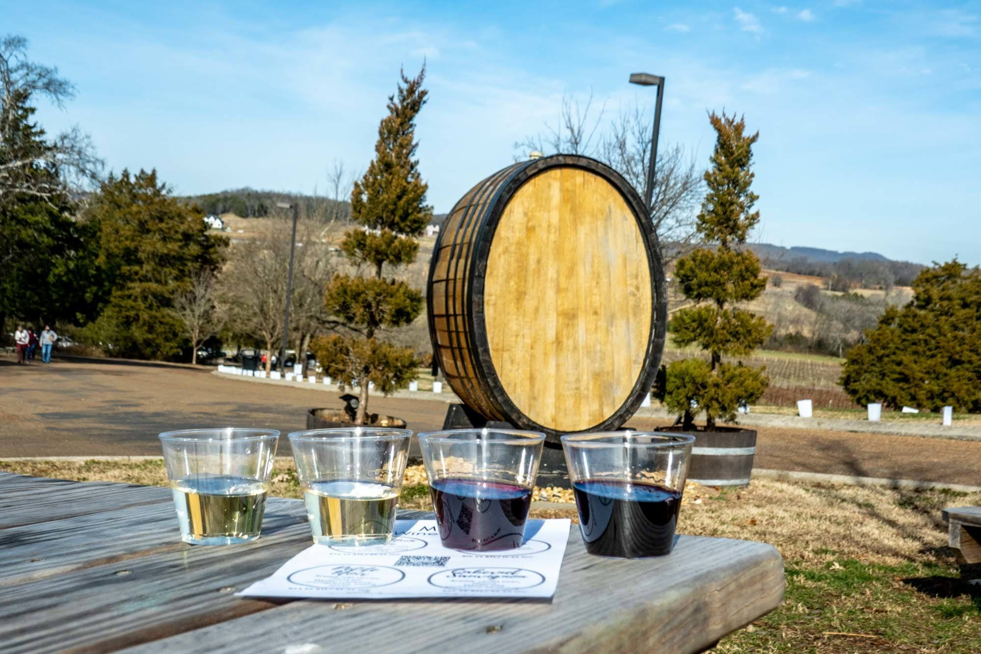 Wine tasting flight on a picnic table beside a large wooden barrel