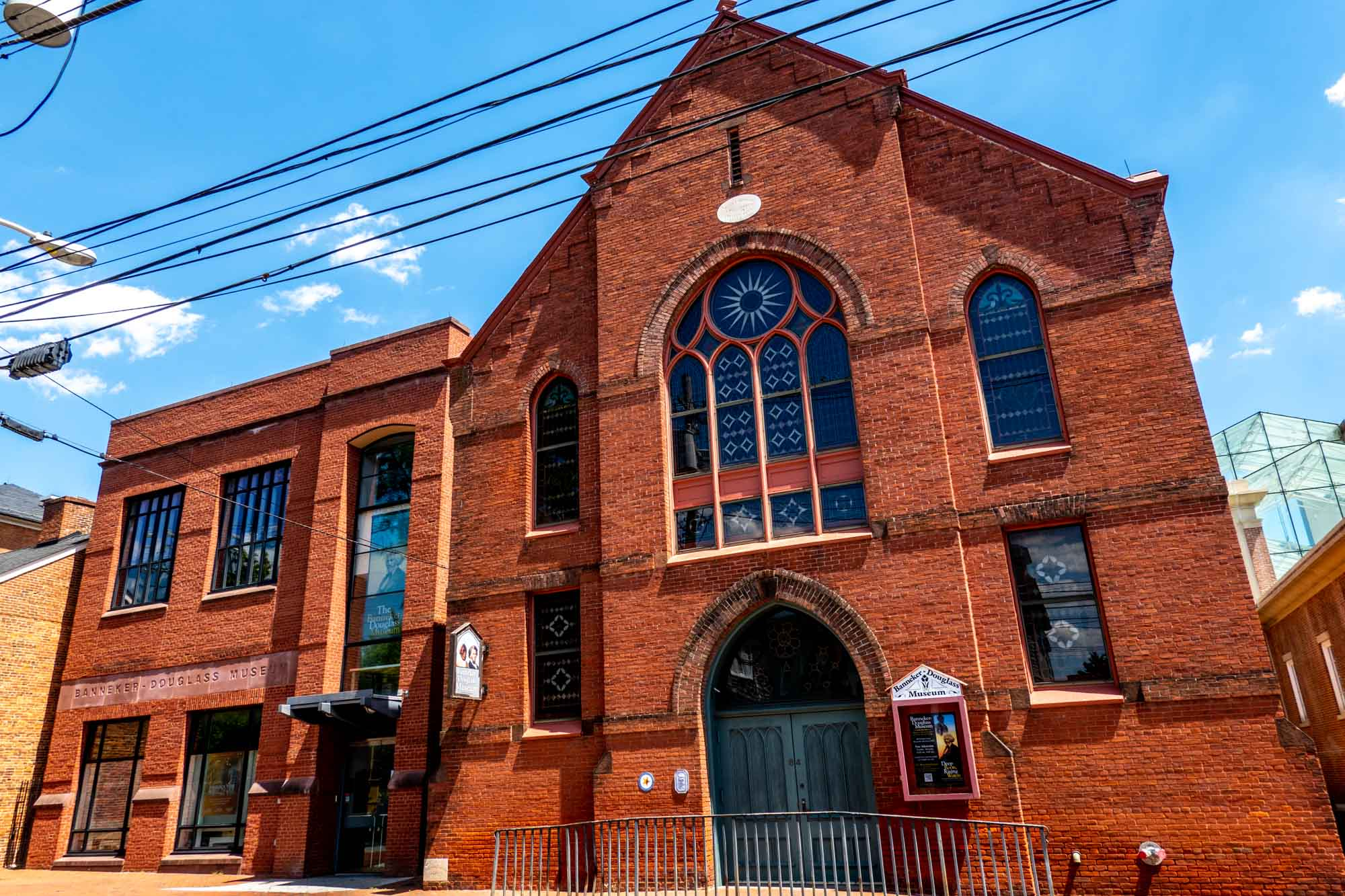 Exterior of a red brick church with stained glass windows