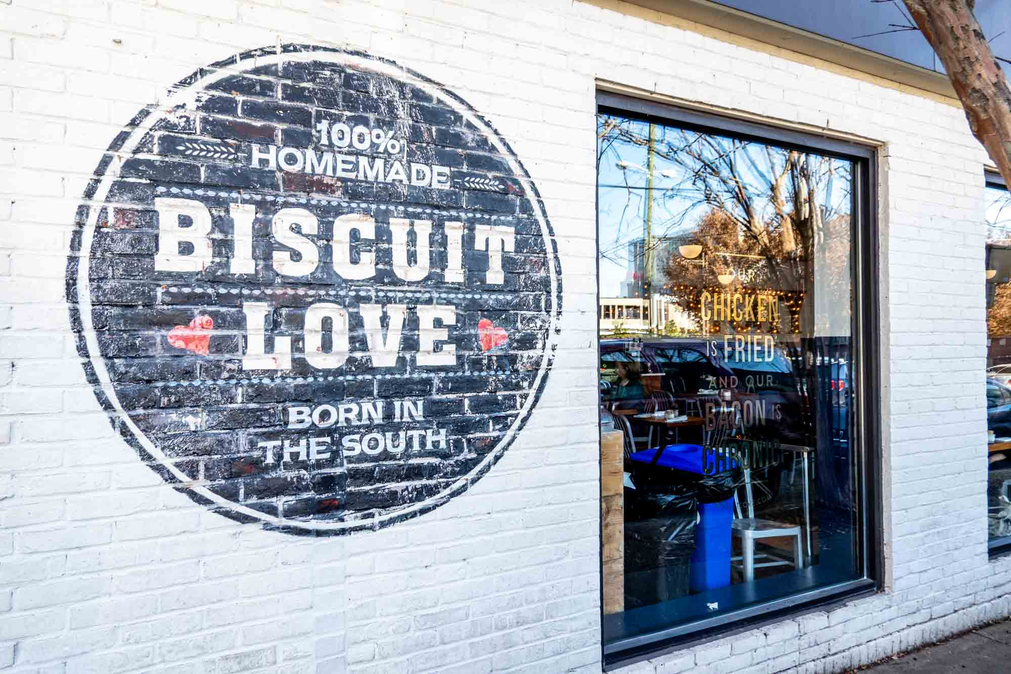 White brick building with a painted sign: Biscuit Love, 100% Homemade, Born in the South