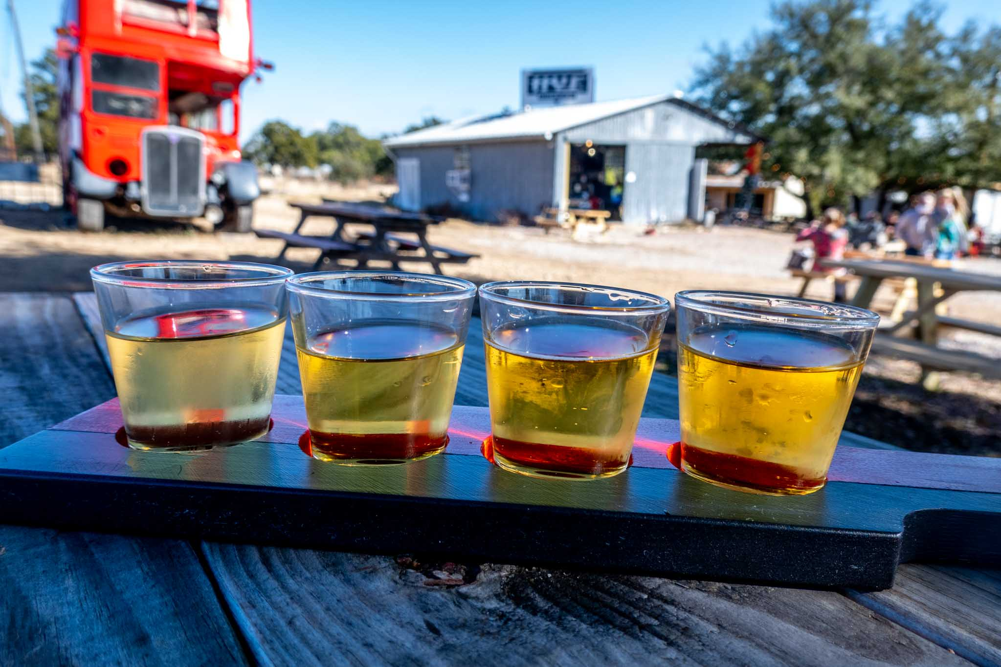 Flight of 4 glasses of cider on a picnic table