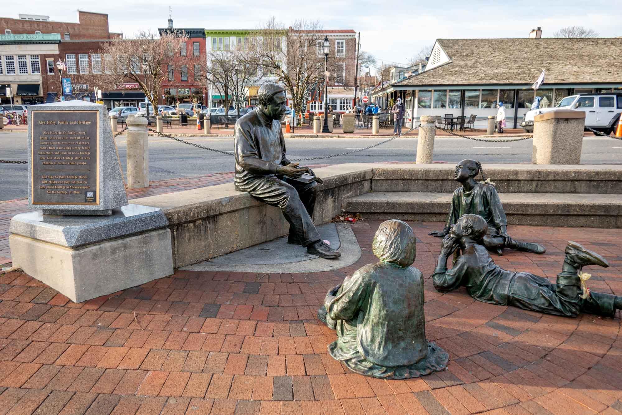 Sculpture of a man reading to three children