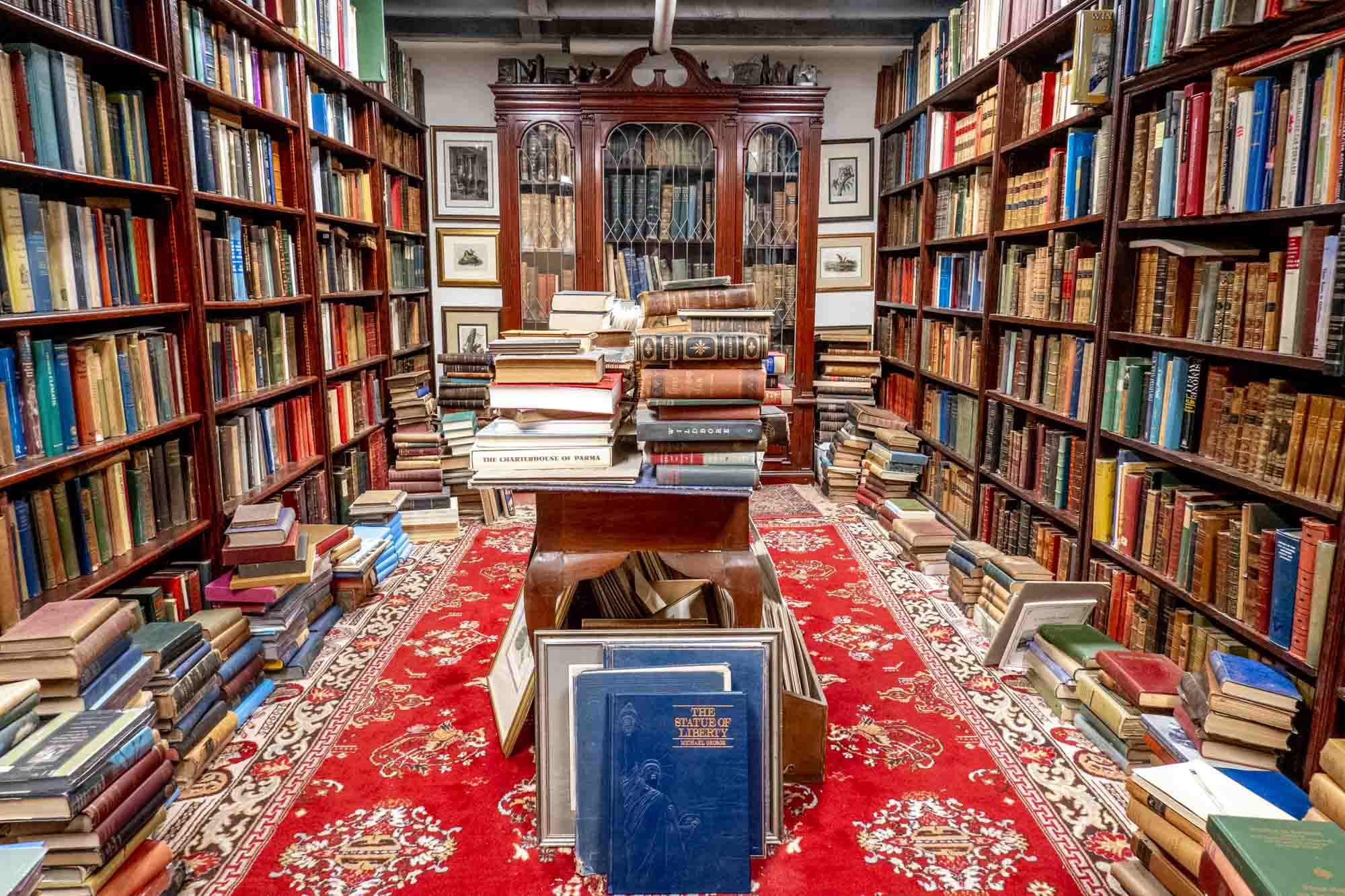 Room full of shelves and tables stacked with books