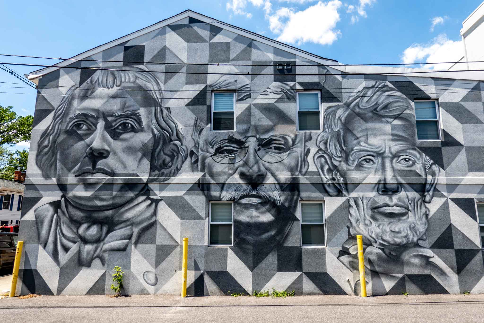 Black, white, and gray street art mural featuring the faces of three men--Abraham Lincoln, Teddy Roosevelt, and James Madison