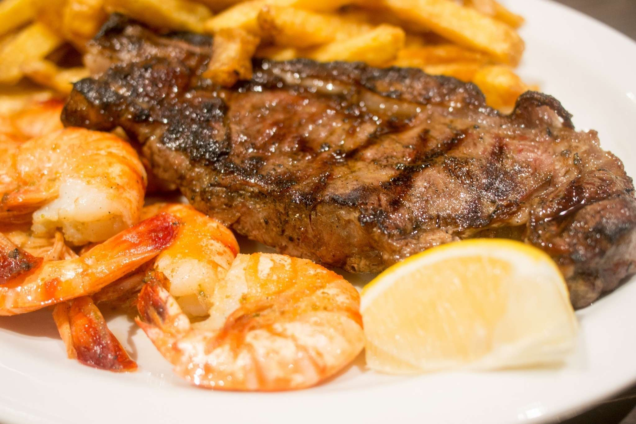 Steak, shrimp, French fries, and lemon wedge on a plate