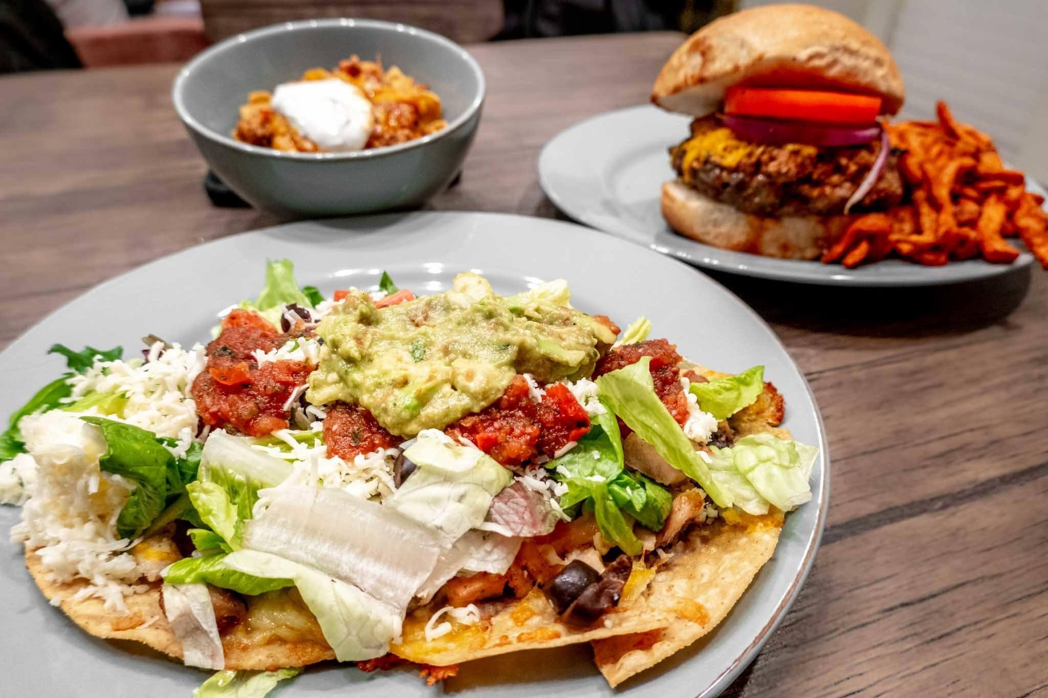 Salad, hamburger, and bowl of Frito Pie on a table