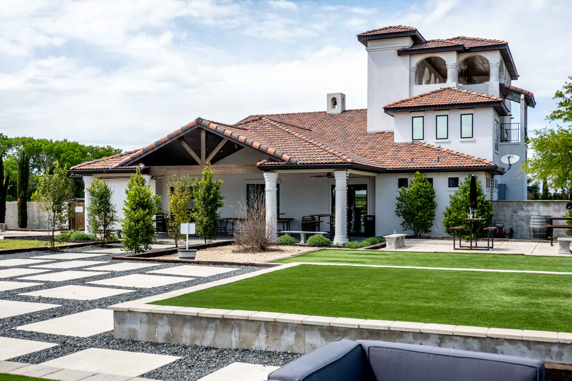 Patio area outside a large white building with a terra cotta tile roof