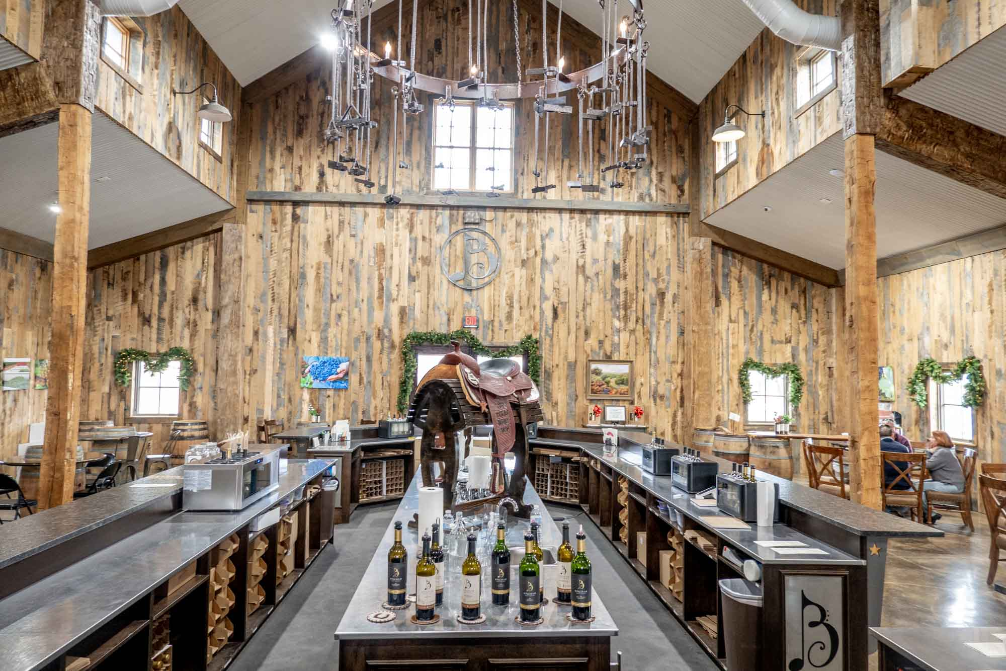 Large room with wood paneling and a bar for wine tasting at the center