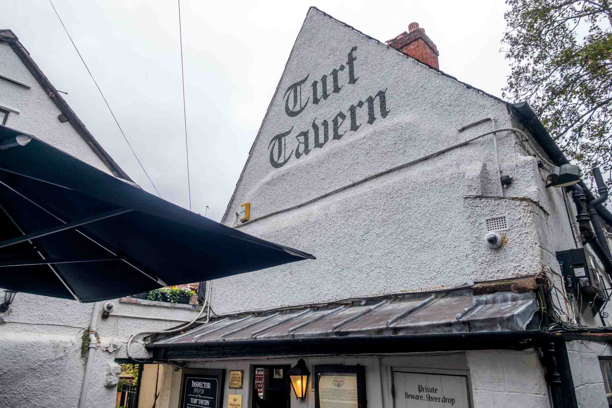 Exterior of a white stucco building with a black sign for Turf Tavern