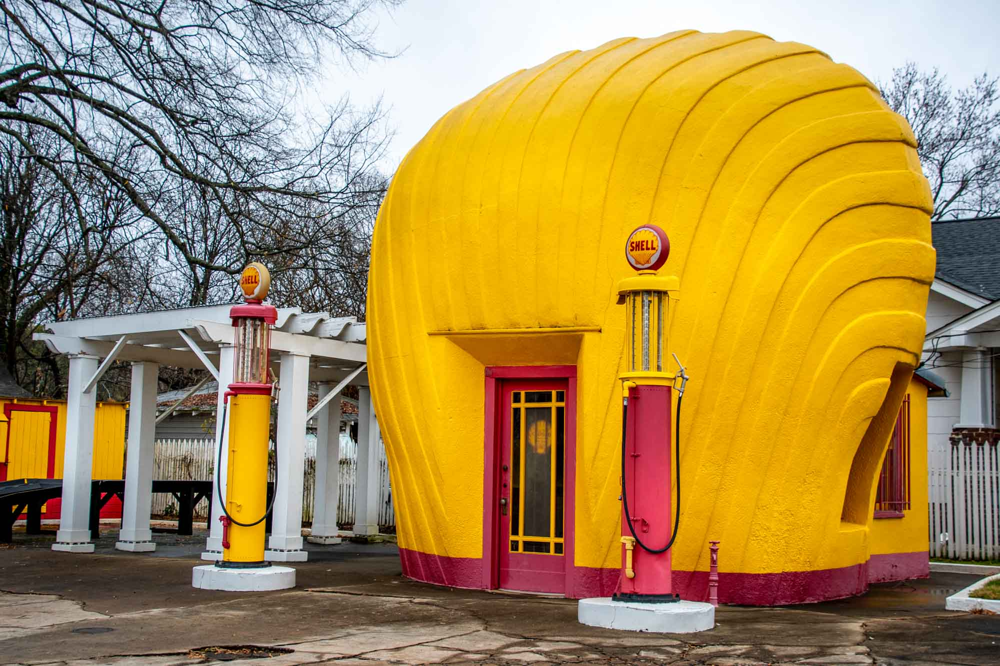 Building shaped like a large yellow clamshell with two gas pumps in front