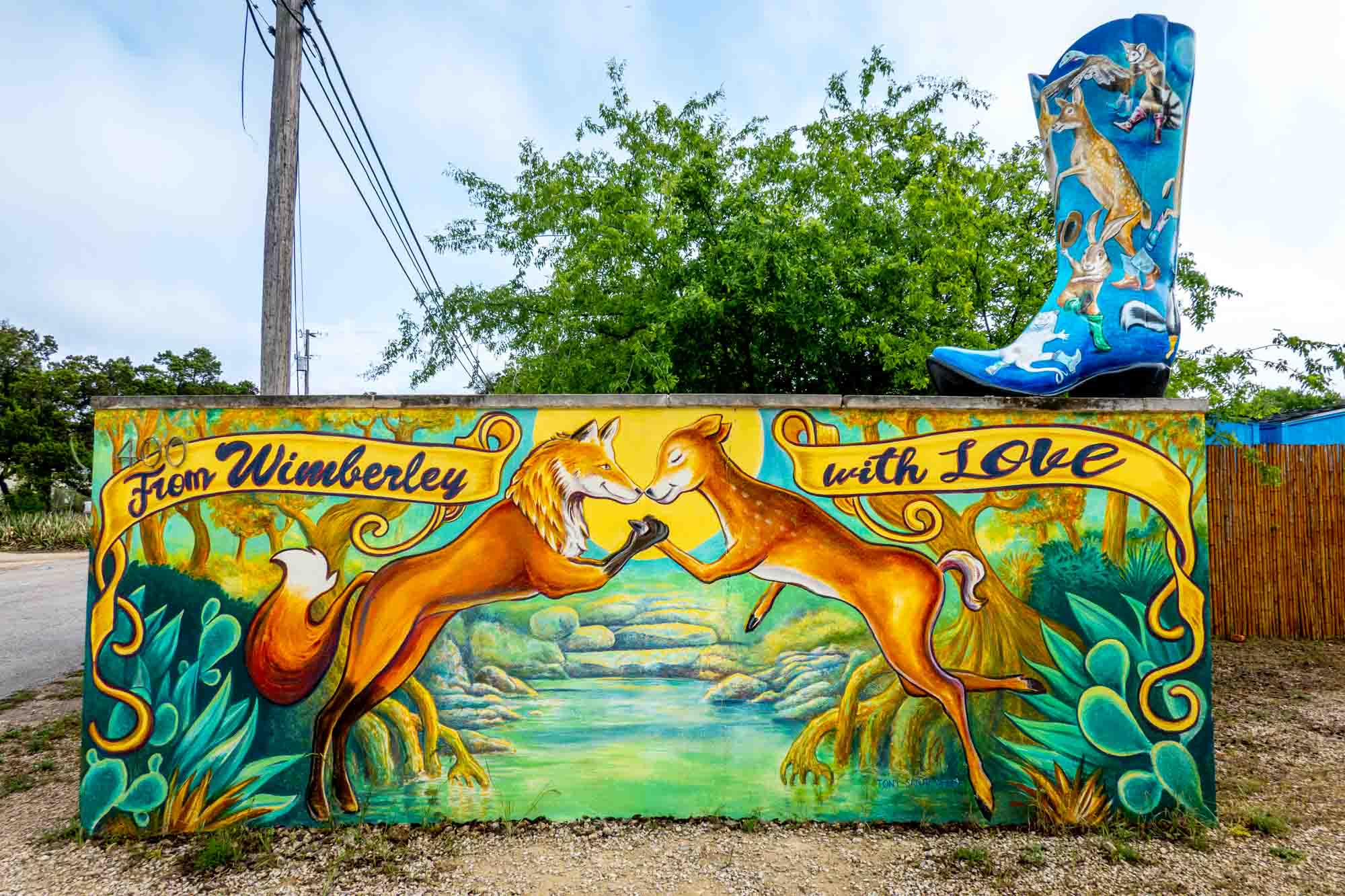 """Mural of a fox and deer clasping paws under a banner that says """"From Wimberley with Love"""""""
