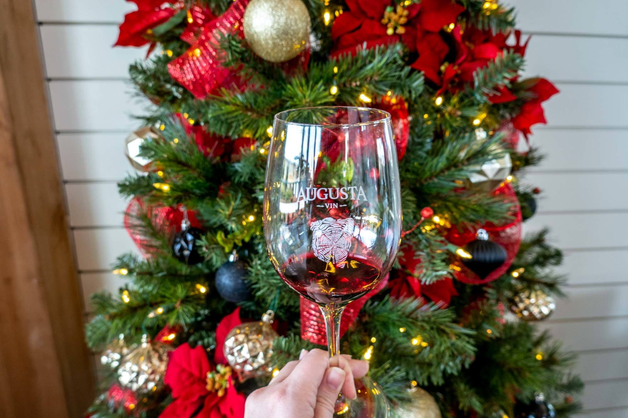 """A wine glass labeled """"Augusta Vin"""" in front of a Christmas wreath"""