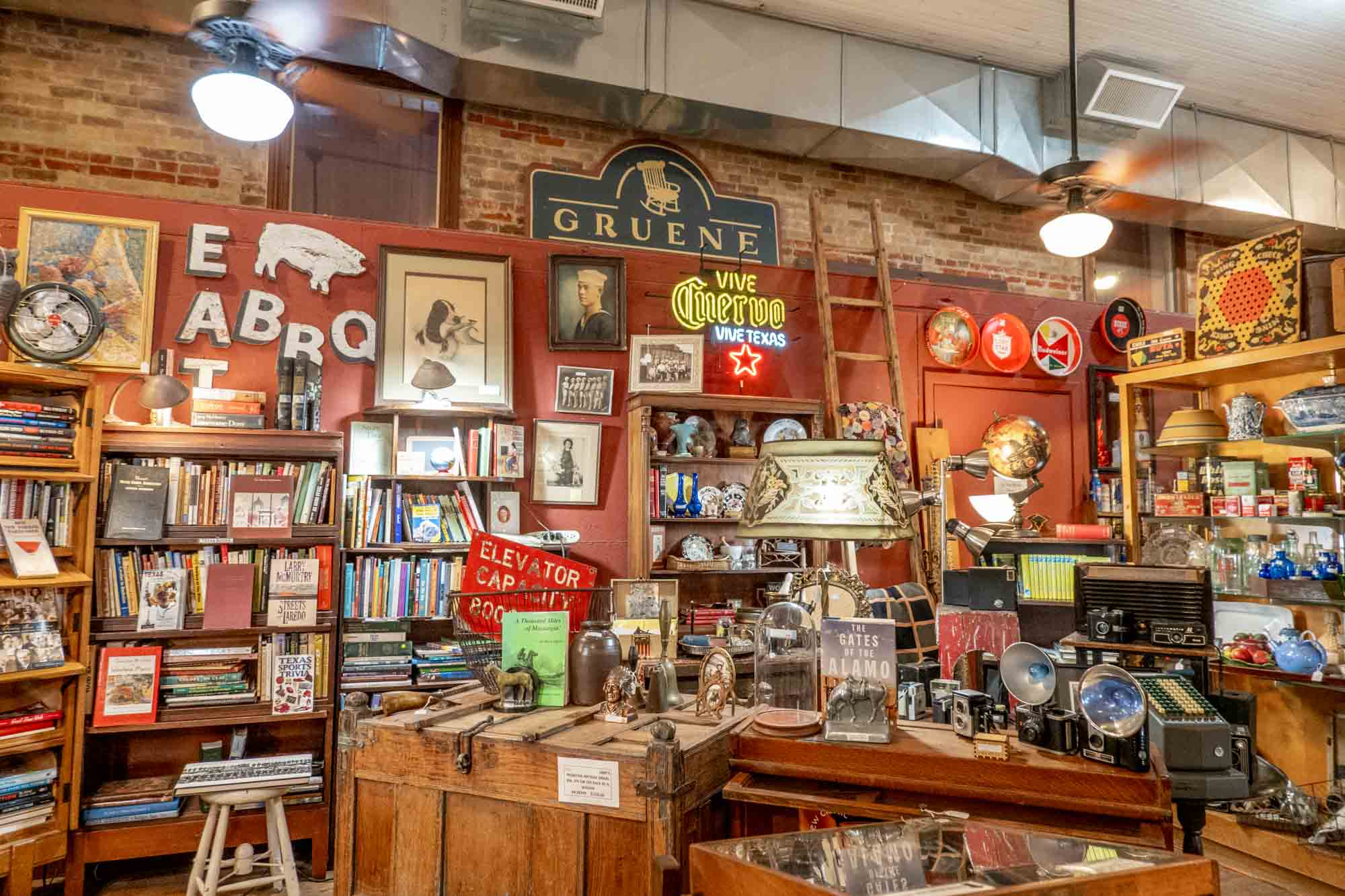 Room filled with books, glassware, signs, and other antiques for sale