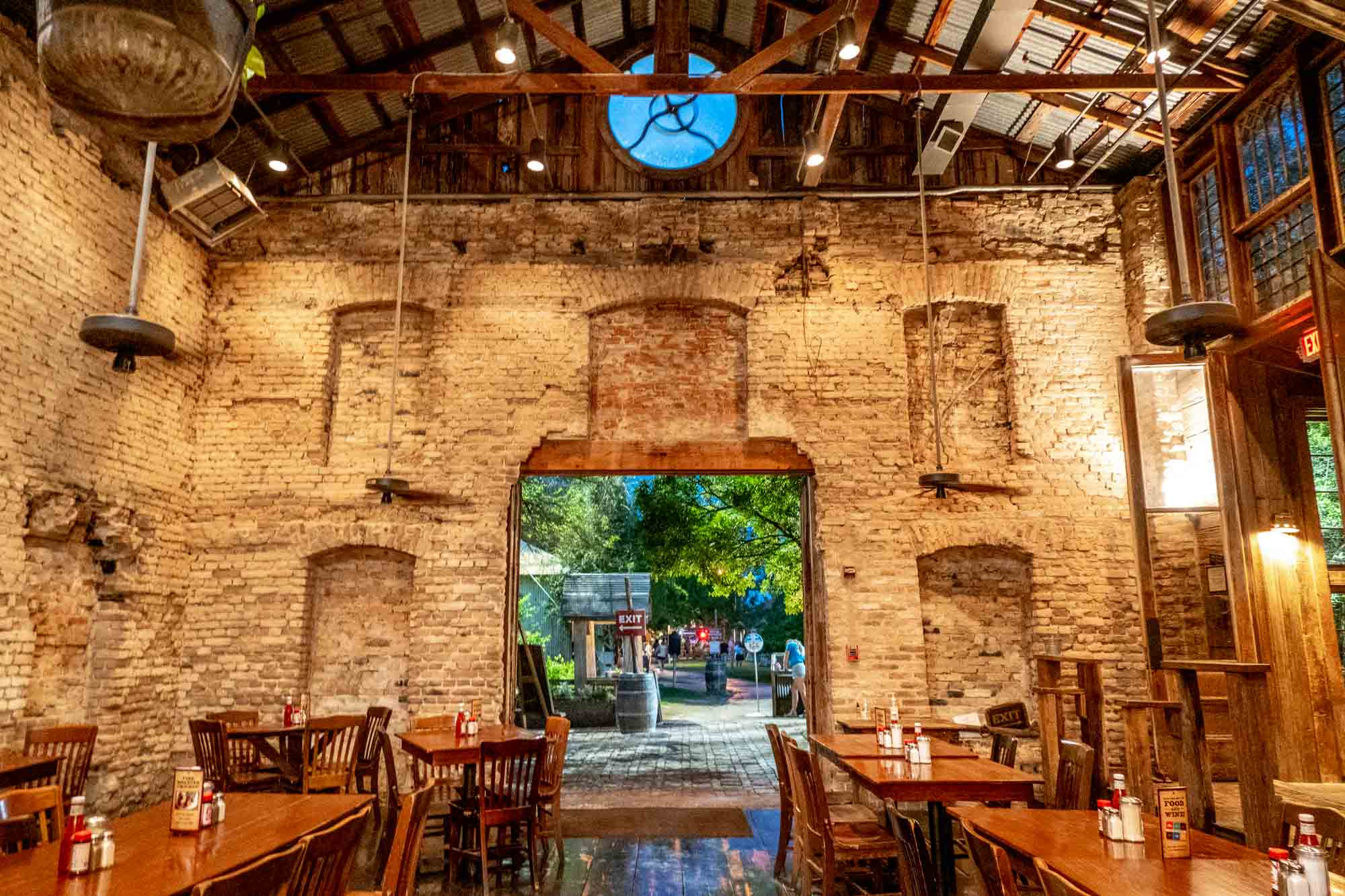 Inside a room with white brick walls filled with restaurant tables and chairs
