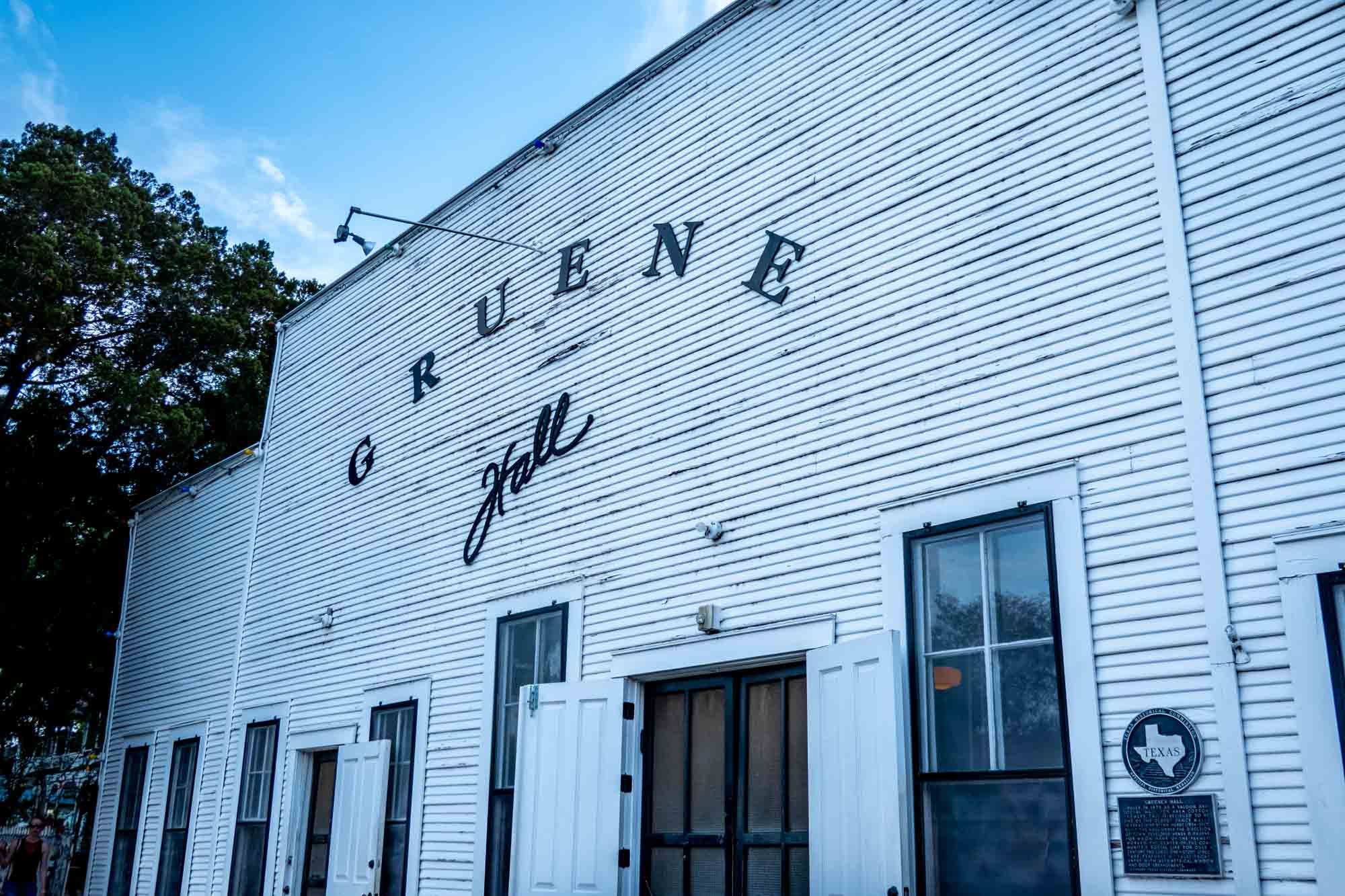 White clapboard exterior of a building with a black sign for Gruene Hall
