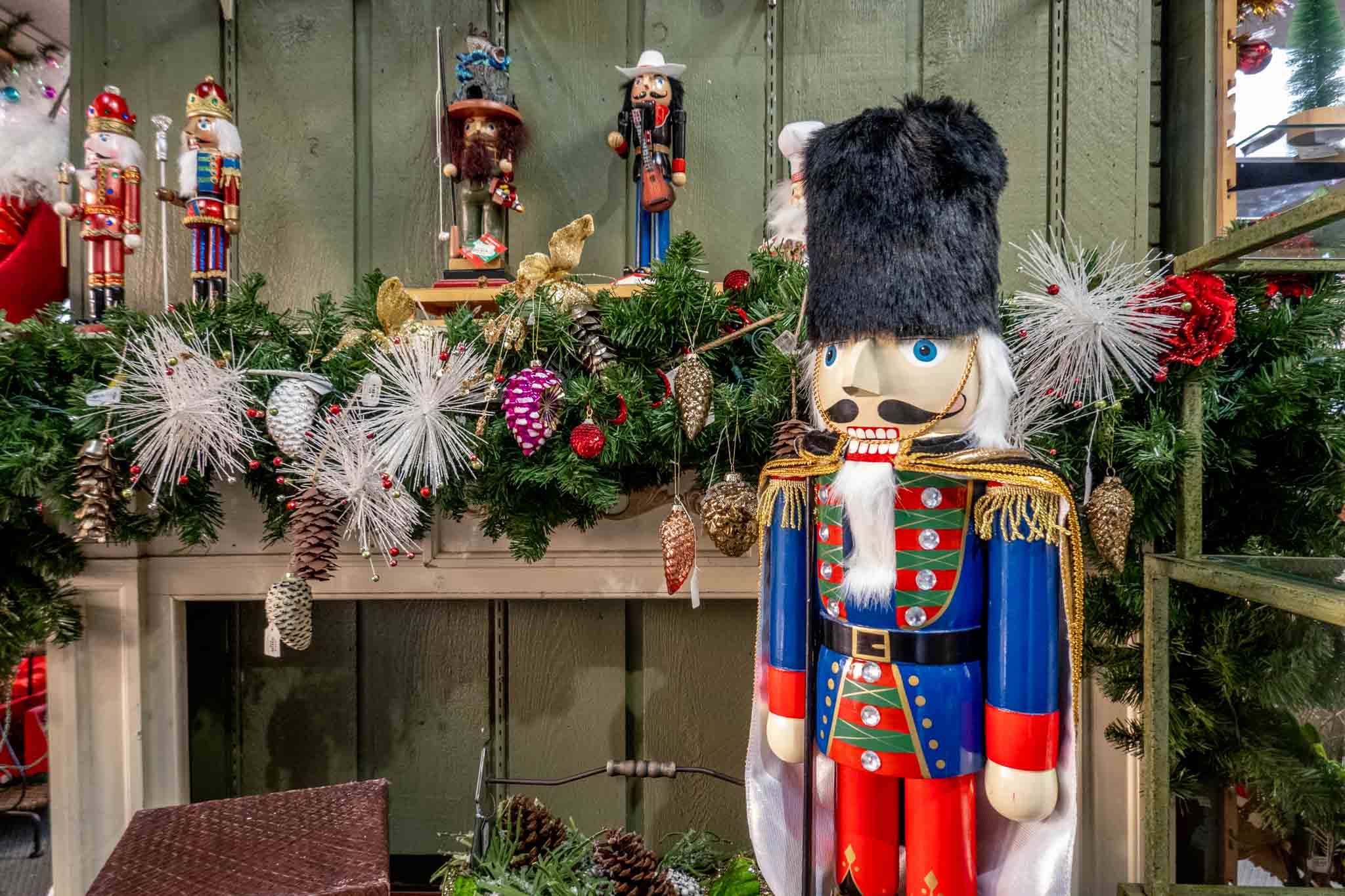 3-foot-tall Nutcracker in front of a mantel lined with small Nutcrackers