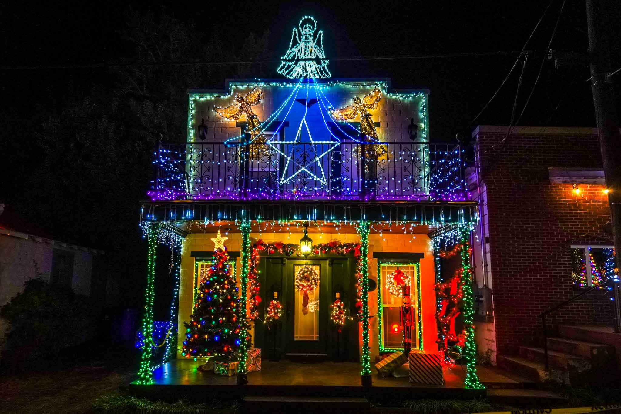 Building decorated with colorful Christmas lights and topped by an angel light sculpture