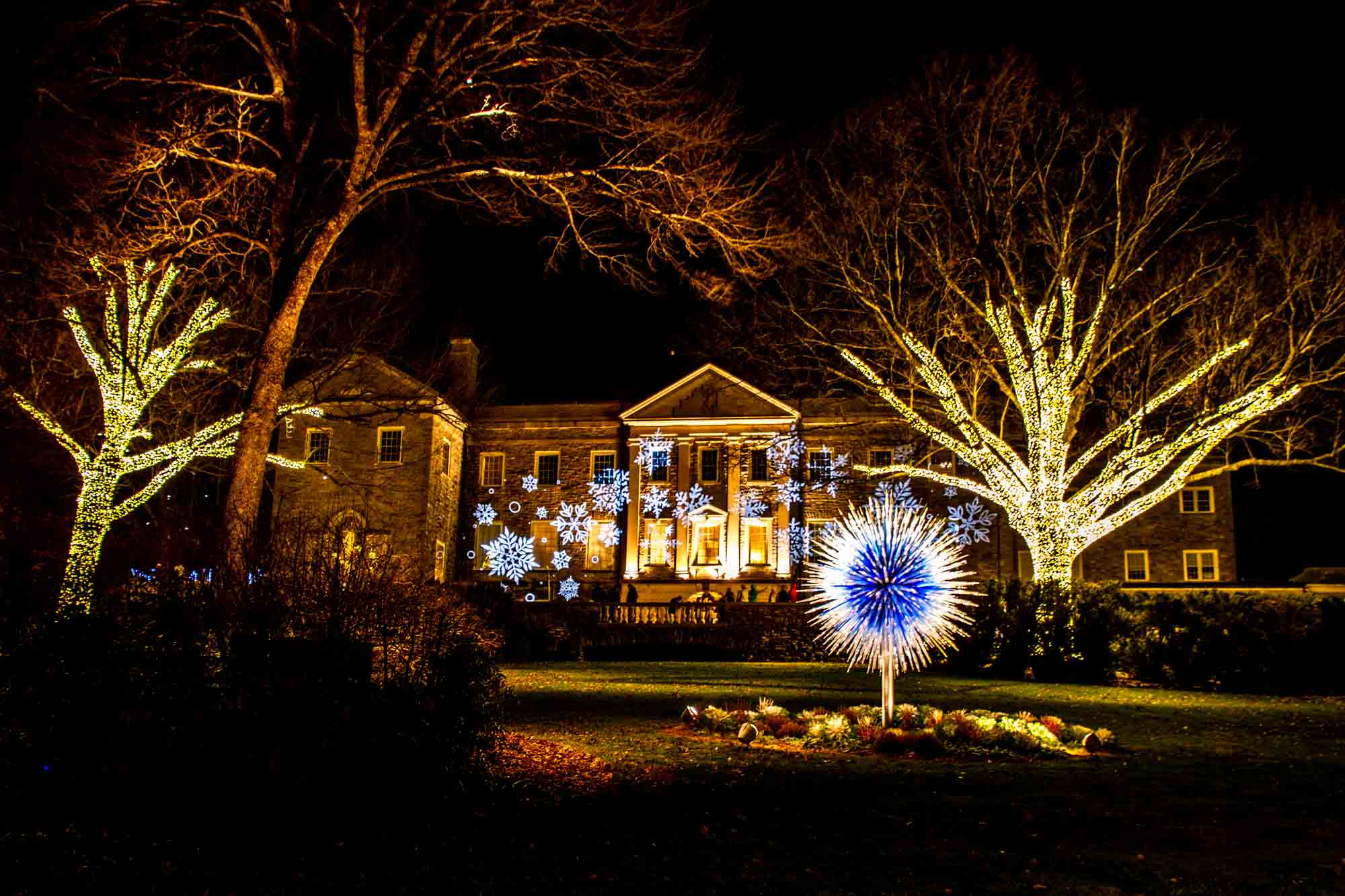 Snowflake lights projected on a mansion facade beside lit up trees and an illuminated blue and white sculpture