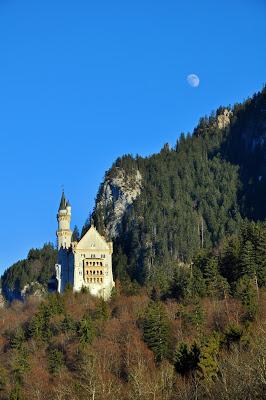 Neuschwanstein Castle with moon above it