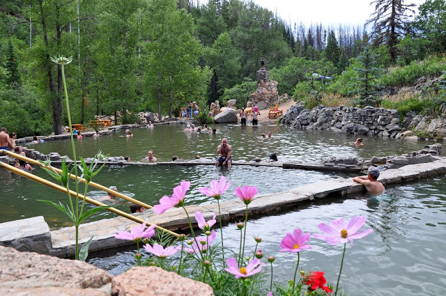 People in the natural pools surrounded by trees and flowers