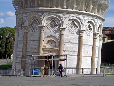Guard standing in front of the base of the Leaning Tower of Pisa