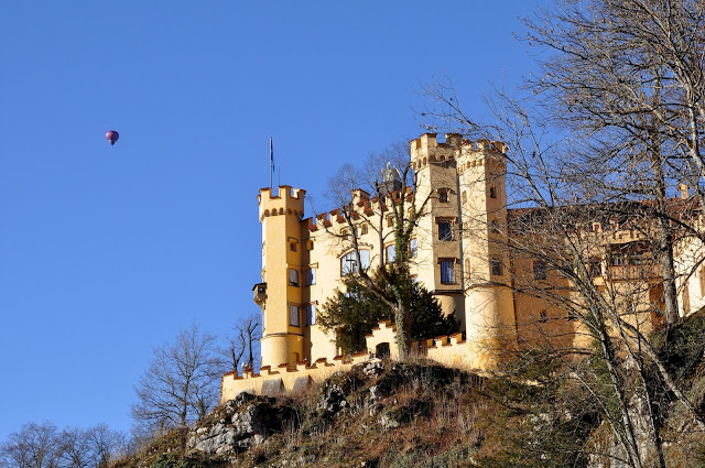 Yellow exterior of Hohenschwangau Castle with hot air balloon in the sky