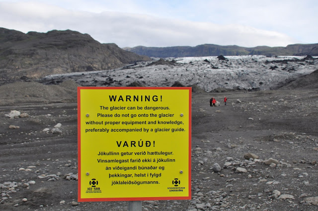 Yellow warning sign about danger on the glacier